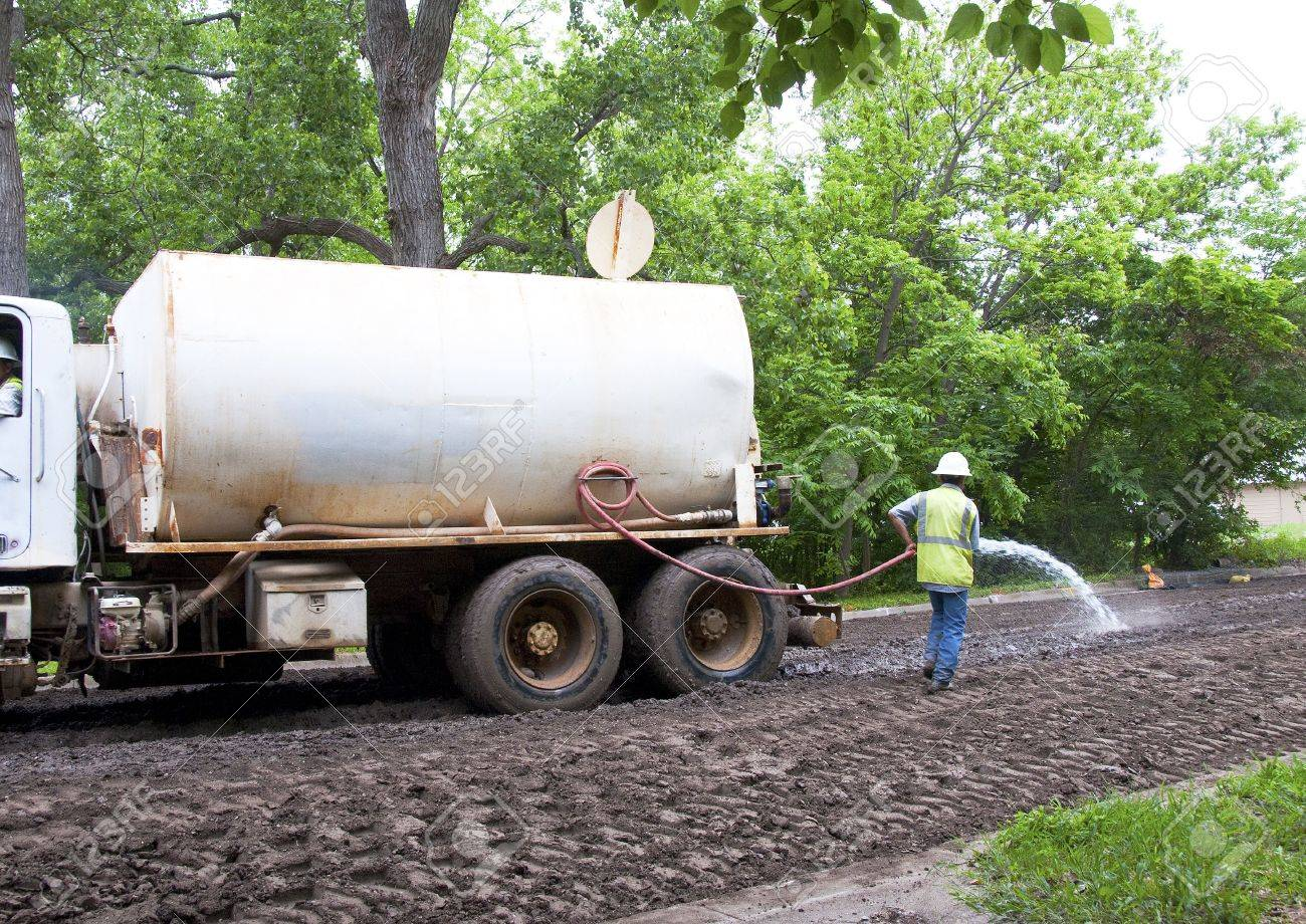 4810845-man-watering-the-dirt-in-the-road-prior-to-grading-and-compacting.jpg